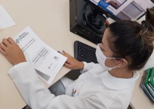 enfermeira lendo manual da regulação de leitos do HEAC